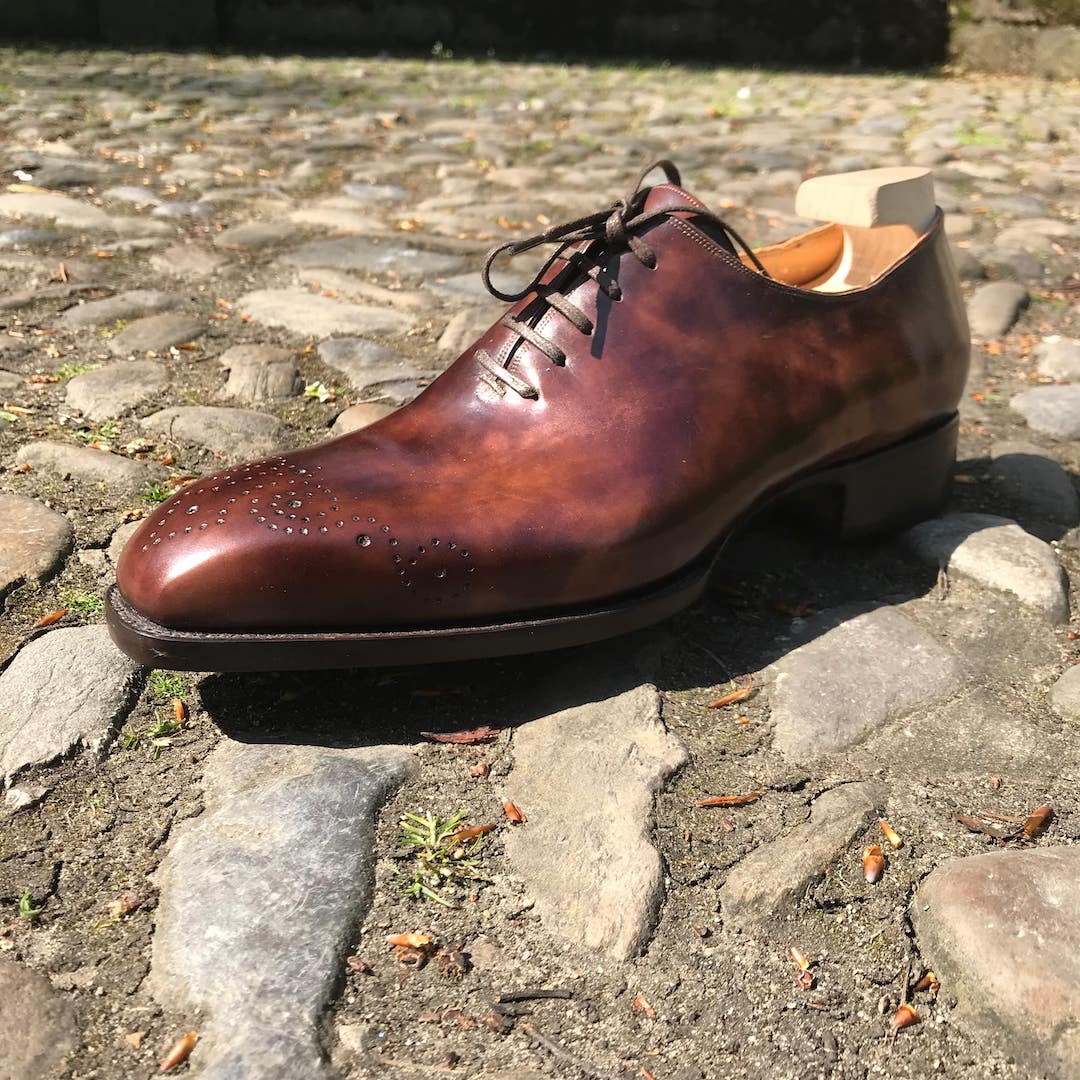 brown hand punched toe medallion shoes on cobble stones
