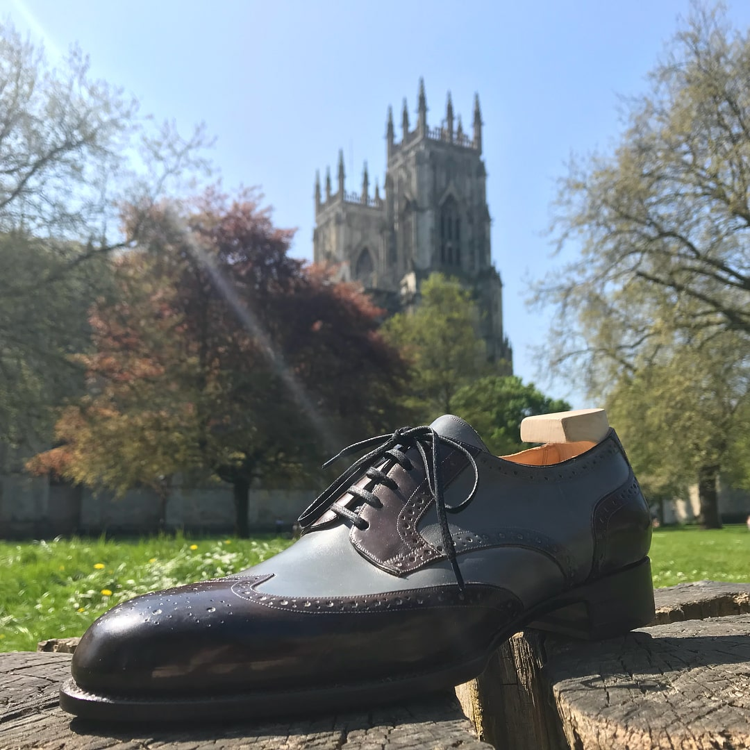 bespoke black and blue shoe in front of the York minster